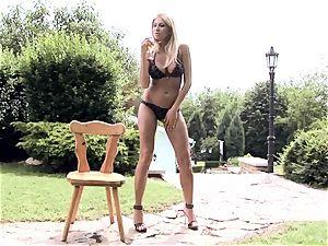 Clara G in ebony lingerie seducing on chair outdoor